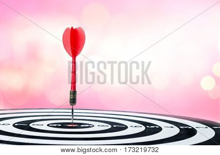Close up shot red dart arrow on center of dartboard over bokeh background with copyspace metaphor to target success winner concept