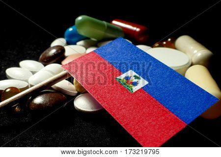 Haitian Flag With Lot Of Medical Pills Isolated On Black Background