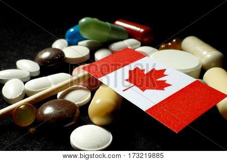 Canadian Flag With Lot Of Medical Pills Isolated On Black Background