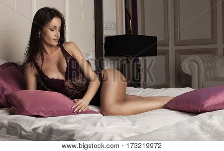 Young Sexy Brunette Woman In Sexy Purple Lace Lingerie Lying On The Bed In Luxury Apartment