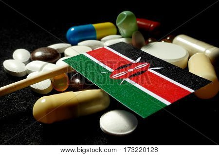 Kenyan Flag With Lot Of Medical Pills Isolated On Black Background