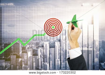 Businessman's hand aiming at taget. Business chart and city background. Targeting concept