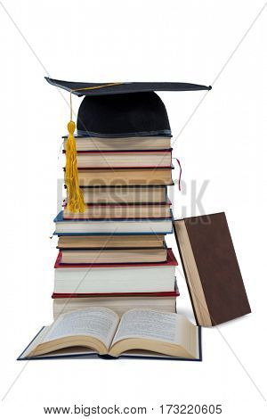 Mortarboard on stack of books on white background