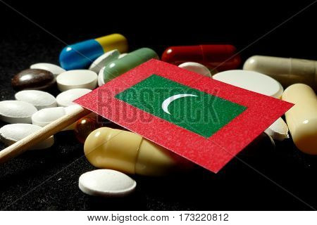 Maldivian Flag With Lot Of Medical Pills Isolated On Black Background