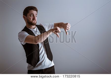 portrait of handsome young man in white shirt showing gesture thumbs down on gray background.