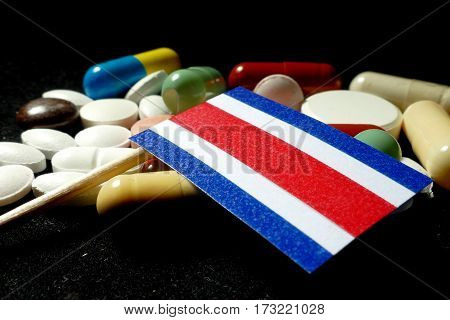 Costa Rican Flag With Lot Of Medical Pills Isolated On Black Background