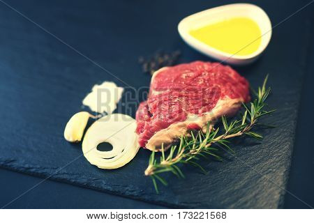 Raw beef steak on a cutting board with rosemary and spices.