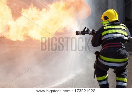 Fireman fighting fire during training. Firefighter in action.
