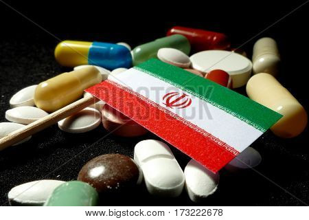 Iranian Flag With Lot Of Medical Pills Isolated On Black Background
