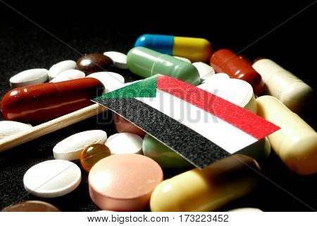 Sudanese Flag With Lot Of Medical Pills Isolated On Black Background