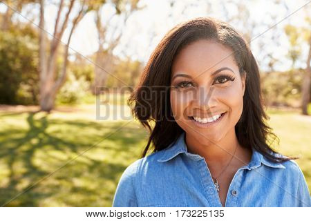 Head And Shoulders Portrait Of Young Woman In Park