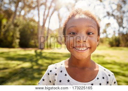 Outdoor Head And Shoulders Shot Of Young Girl In Park