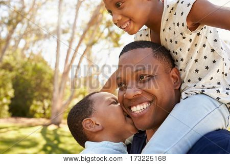 Father Carrying Children On Shoulders As They Walk In Park