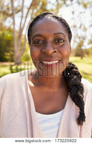Head And Shoulders Portrait Of Mature Woman In Park