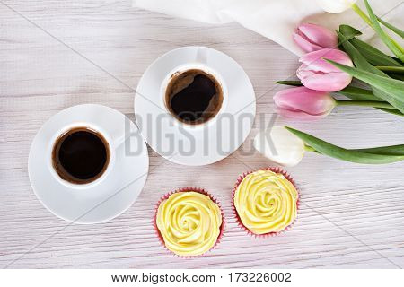 Tasty cupcakes on bright background. vanilla cupcakes with pink and yellow cream selective focus