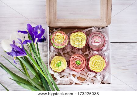 Cupcake packaging delivery box vanilla cupcakes with pink and yellow cream selective focus close up