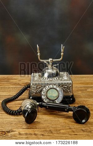 Vintage old telephone on a wooden table.