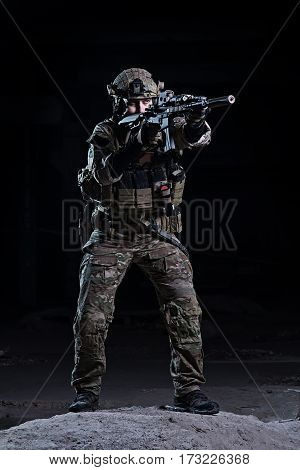 Soldier in uniform body armor and helmet holding rifle on dark background