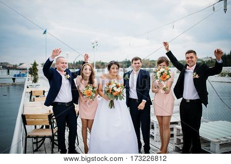 Wedding Couple With Bridesmaids And Best Mans Stay On The Pier Berth At Cloudy Day.
