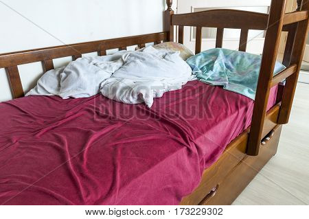 Unmade child bed with crumpled red and white bed linens and pillow.
