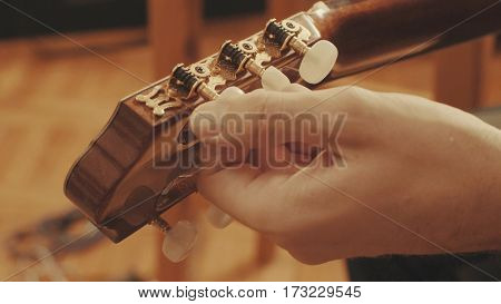 Guitarist's hands tuning the acoustic guitar close-up