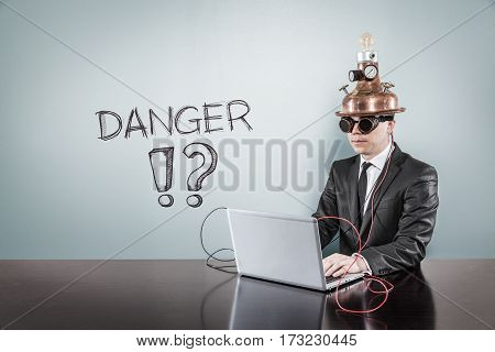 Danger text with vintage businessman using laptop at office