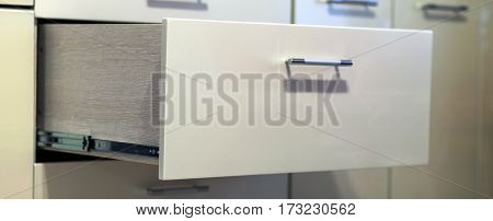 A detail close up shot of a laminate stylish kitchen drawer