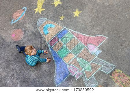 Funny little kid boy flying in universe by a space shuttle picture painting with colorful chalks. Creative leisure for children outdoors in summer.