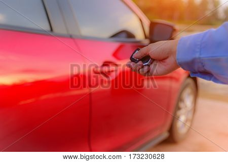 Woman's hand open the car with car remote key at car park.