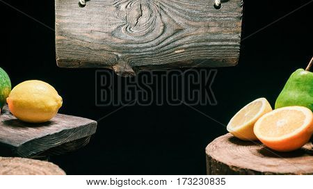 Rustic wood sign hanging above wood boards with oranges, pears and lemons. Isolated over black background