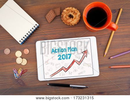 Action Plan 2017 concept. Tablet on an old wooden table.