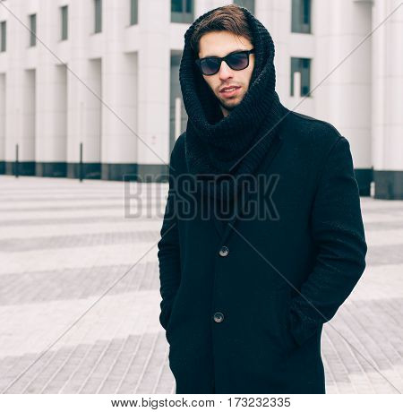 Fashion and Style. A young man in a fashionable black coat, sunglasses and snood posing near the business center. Close up. Outdoor. Streetstyle