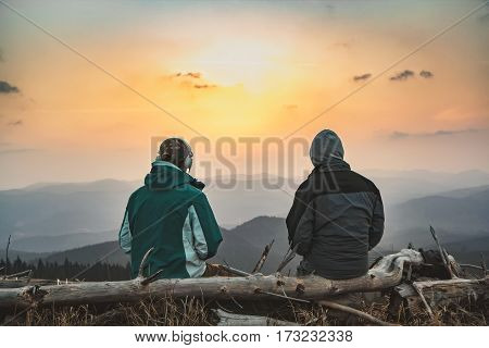 Two young men watching the sunrise in the mountains