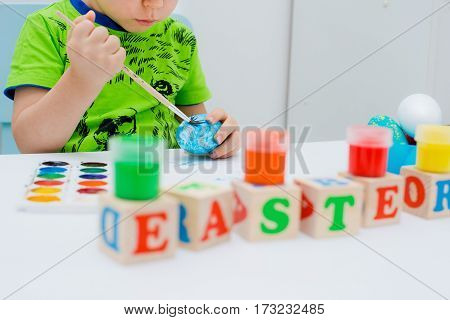 Child paints easter eggs on a white background