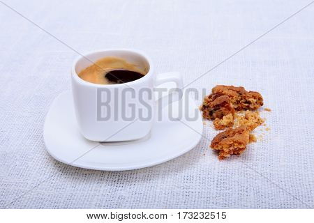 Cup of espresso coffee on white plate with pieces cookie on white background.
