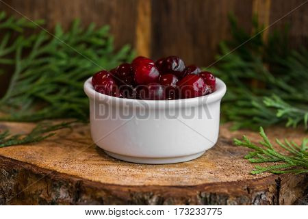 Pickled cranberries in a sweet syrup in a white bowl on the wooden background with the leaves of juniper