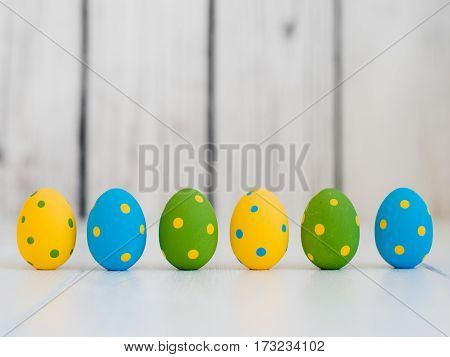 easter eggs standing in a row on a white wooden background