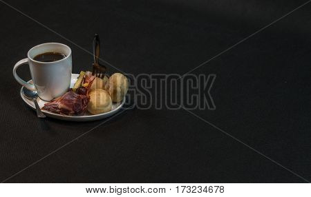 small snack consisting of meat and sausages French cheeses fresh crunchy bread black coffee with a tasty snack