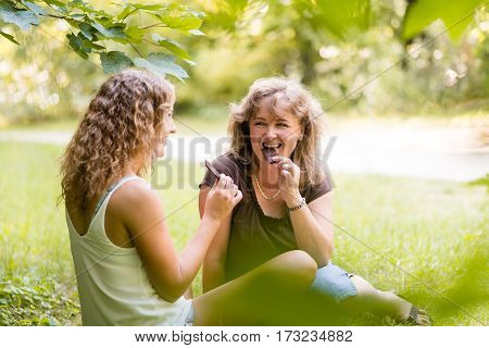 Mother with daughter having fun as they bite chocolate
