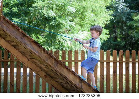 Little Toddler Boy Kid Having Fun At A Wooden Playground Outdoor