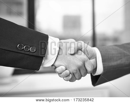 two corporate businessmen shaking hands in office black and white.