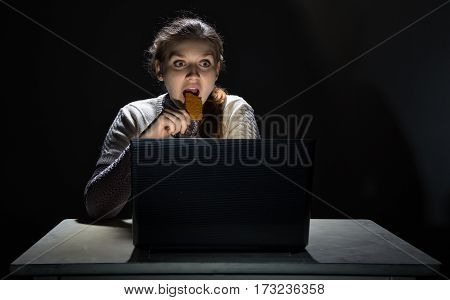 Scared woman watching movie and eating snack on black background