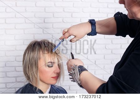 Women's haircut. Hairdresser, beauty salon. Professional hairdresser making stylish haircut. Hairdresser cutting woman bangs hair. Process of hair cutting with use open-blade