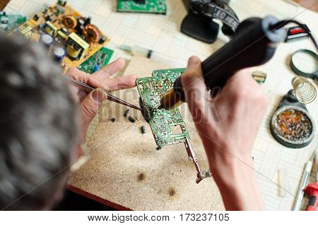 Closeup of a technician's hands soldering a electronic devices. top view