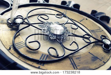 Old vintage wall clock with roman numbers and ornamental metal author design heart instead of clockwise. Abstract composition for your design.