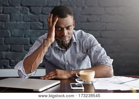 Unhappy African Businessman Feeling Stressed And Frustrated, Facing Financial Troubles, Leaning Elbo