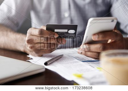 Close-up View Of African Man's Hands Holding Plastic Credit Card And Smart Phone. Dark-skinned Busin