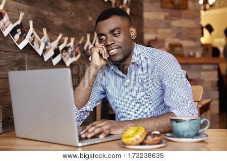 Indoor Shot Of Attractive Young Dark-skinned Employee In Shirt Using Generic Laptop Computer, Surfin