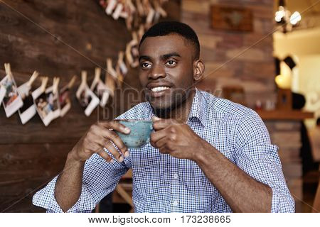Indoor Portrait Of Handsome Young Dark-skinned Entrepreneur Or Office Worker Holding Cup Of Coffee,