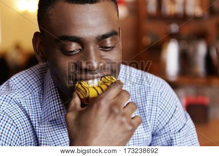 Headshot Of Attractive Young African-american Businessman Biting Doughnut, Enjoying Junk Food During